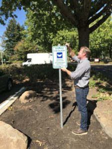 Construction finished, Doug Schleichert installs the Reserved for Salmon sign, in a parking space turned stormwater treatment facility.