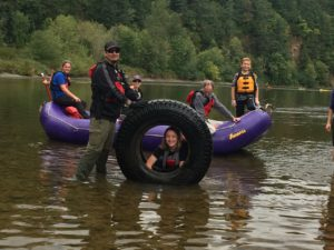 Volunteers pose for a picture on the Sandy river with a tire they pulled out of the water