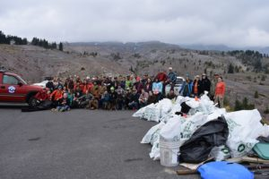 Volunteers pose with dozens of trash bags in front of Mt hood